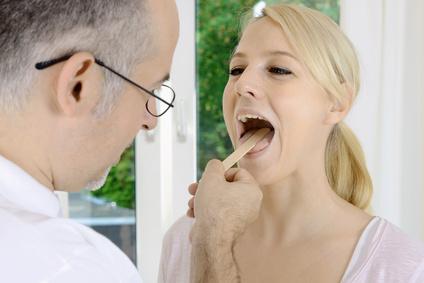 Arzt bei der Akupunktur Zungendiagnose